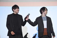 泰江和明(左)を見ずにマイクを手渡す輝山立(右)。