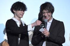 抽選会にて当選番号を読み上げる高崎翔太(右)と、ルーペを使って高崎の手助けをする玉城裕規(左)。