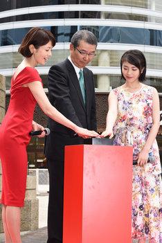 新・ゴジラ像お披露目のため除幕ボタンを押す登壇者。左から沢口靖子、島谷能成、浜辺美波。
