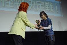 対決の勝者にトロフィーを手渡すアイデンティティ田島(左)。