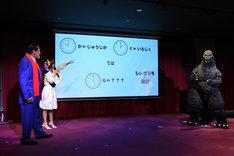 ゴジラから出題された謎解きに挑戦するアントニオ猪木(左)。