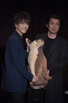 智の愛犬・コウの木彫りを抱く岩田剛典(左)と永瀬正敏(右)。