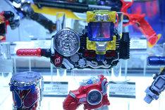 バンダイブース「仮面ライダービルド」コーナーより、「変身ベルト DXビルドドライバー」と「DXジーニアスフルボトル」。