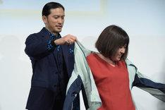 受賞者の女性に赤松運送のジャケットを着せる長瀬智也(左)。