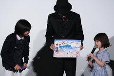 佐々木みゆ(右)の描いた似顔絵を見る城桧吏(左)とリリー・フランキー(中央)。