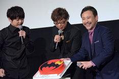 バットマンマークがデザインされたケーキを見せる登壇者たち。