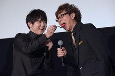 梶裕貴(左)が山寺宏一(右)にファーストバイトを行う様子。