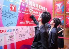 パネルにサインする池松壮亮(手前)と松居大悟(奥)。