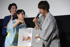 箱の中で葵わかな(左)へセミの模型を手渡す佐野勇斗(右)。