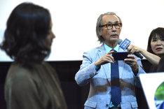 スマートフォンでキャストを撮影しようとする木村大作(中央右)。