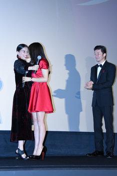 抱き合う土屋太鳳と芳根京子を見守る浅野忠信(右)。