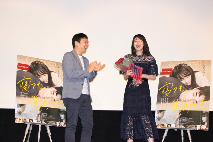 濱口竜介(左)から、バラの花束と牛腸茂雄の写真集を贈られた唐田えりか(右)。
