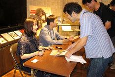 サイン会を行う唐田えりか(左手前)と濱口竜介(左奥)。