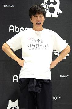 カメラマンからの「やってやる!の表情」というリクエストに応じる田中圭。