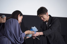 吉田羊(左)にプレゼントを手渡す佐野玲於(右)。
