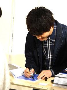 ファンの前でサインを書き込む多和田任益。