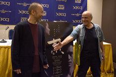 写真撮影に応じている塚本晋也(左)のもとへ近寄り、握手を求めるアミール・ナデリ(右)。