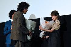 斉藤和義(左)からオレンジ色のバラの花束を受け取る有村架純(右)。
