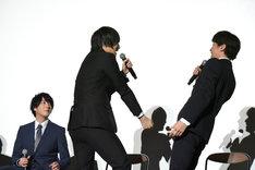 富田健太郎(右)を相手に、刀を振るう動きを披露する荒牧慶彦(中央)。