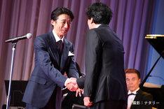 本木克英(右)と握手する高橋一生(左)。