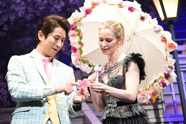 エミリー・ブラント(右)に桜吹雪の小道具を見せる谷原章介(左)。