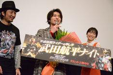 「平成仮面ライダーの申し子」と書かれたボードを見て、「やめてよ!」と照れる武田航平(中央)。