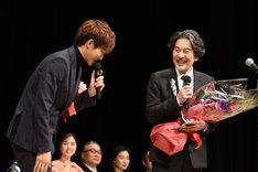 役所広司(右)から髪色をいじられる松坂桃李(左)。