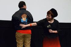 プロデューサーの諏訪道彦が着用してきたブルゾンの刺繍を見せる伊倉一恵(右)。