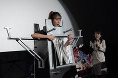 装置の背後から浅川梨奈の体を貫き、あのの手が現れた様子。