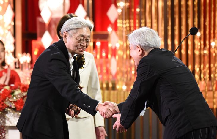 細野晴臣(左)が、2018年の受賞者・鈴木慶一(右)と握手を交わす様子。