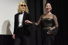 """""""出会って15分""""のローランド(左)にエスコートされながら登壇した真矢ミキ(右)。"""