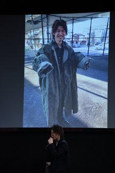 """""""コートがデカすぎて笑っている""""オフショットを紹介する横山涼。"""