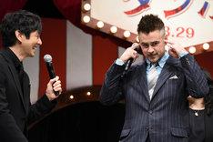 西島秀俊(左)が自分の話をすることを知り、耳をふさぐコリン・ファレル(右)。