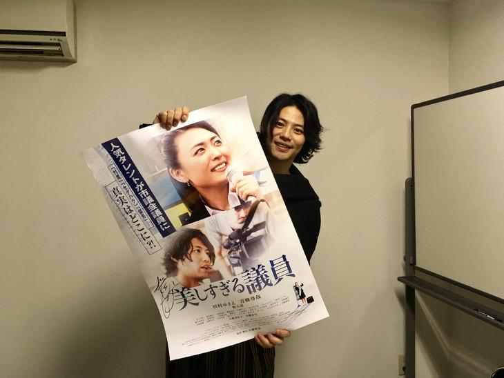 「美しすぎる議員」のポスターを持つ青柳尊哉