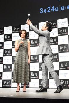 カラオケで尾野真千子(左)の代わりにマイクを持つ様子を再現する安田顕(右)。