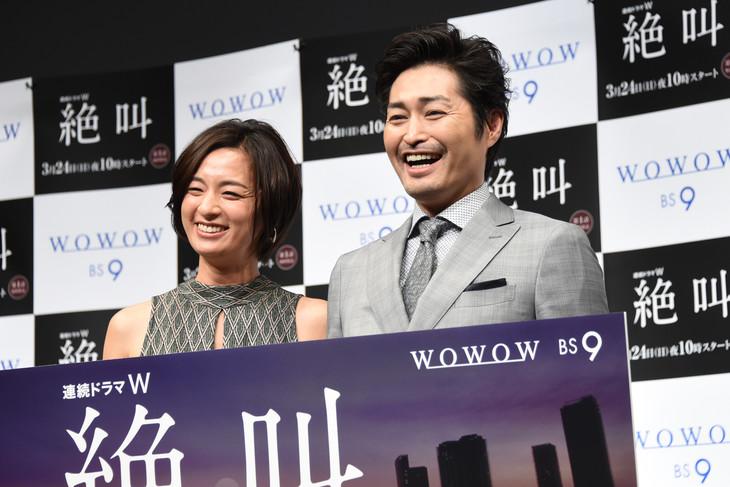 「連続ドラマW 絶叫」第1話完成披露試写会の様子。「怖い顔してください」というカメラマンからのリクエストに、この日一番の笑顔で応える尾野真千子(左)、安田顕(右)。