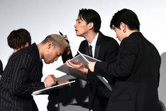 関口メンディー(左)の頭皮を見ながら、白石聖の似顔絵を描く町田啓太(中央)。