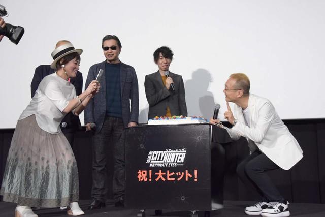 誕生日ケーキと神谷明を撮影をする伊倉一恵(左)。