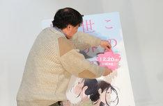 ポスターパネルに公開日の書かれたシールを貼る片渕須直監督。