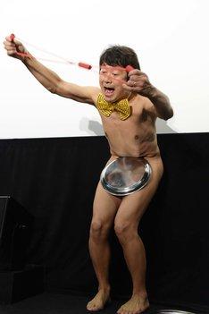 大橋彰(アキラ100%)がお盆を落とさないように筋トレ用のゴムを引っ張る様子。