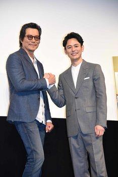 握手を交わす豊川悦司(左)と妻夫木聡(右)。