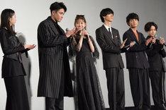 主演を務めた堀未央奈(中央左)に共演者たちが拍手を送る様子。