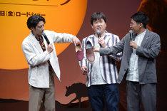 自身の靴と佐藤二朗(中央)の靴のサイズを比べる賀来賢人(左)。