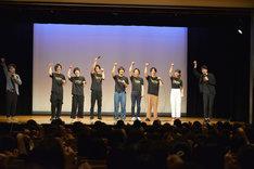 聡太郎(右端)の発声に合わせてシャムニャーンのポーズを取る登壇者たちと観客。