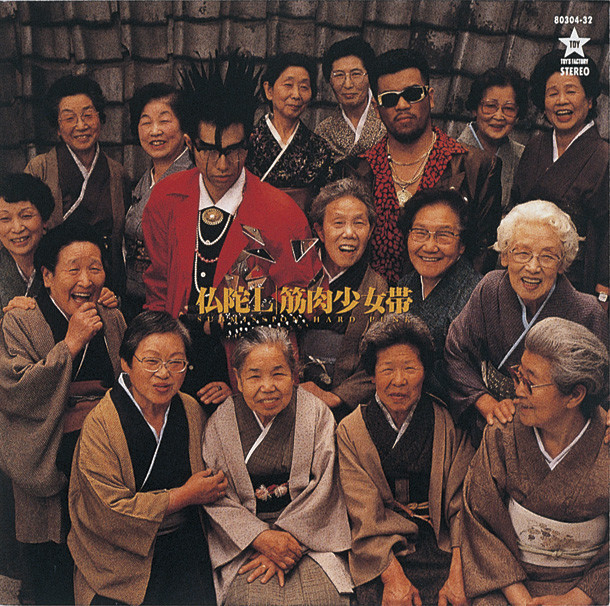 写真は1988年にリリースされたメジャー1stアルバム「仏陀L」ジャケット。大槻ケンヂと三柴江戸蔵(三柴理)の周りを囲む15人のお婆さんは、筋肉少女帯のメンバーではない。