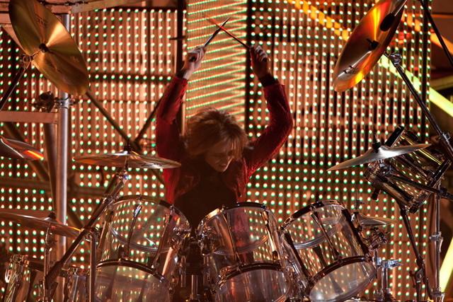 ドラムセットの前に座り、構えるYOSHIKI。