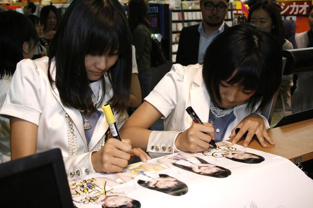 真剣にサインを書く和田彩花(写真左)と小川紗季(右)。