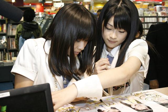 真剣にサインを書く和田彩花(写真左)と前田憂佳(右)。