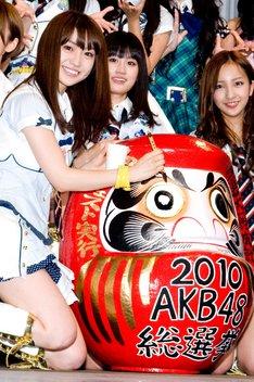 実際の選挙同様に、だるまに目を入れる大島優子(写真左)。
