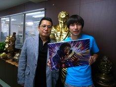 原哲夫(写真左)が描いたイラストを手に、記念撮影をするROCKETMANことふかわりょう(右)。